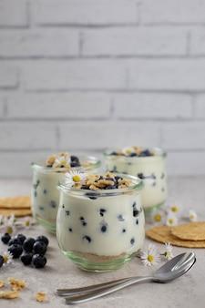 Sobremesa doce em um copo com mirtilos frescos, chantilly, mascarpone, queijo cottage e biscoitos ou waffles em superfície cinza claro