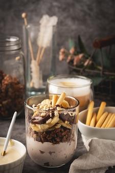 Sobremesa em um copo de iogurte, granola, banana e chocolate com biscoitos, café cappuccino.