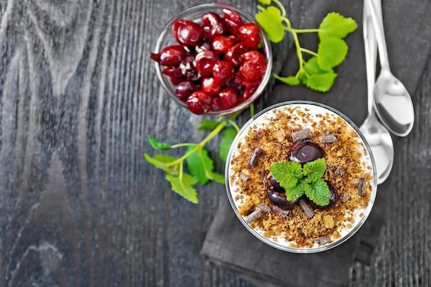 Sobremesa floresta negra de cerejas, biscoito de chocolate e queijo cottage macio com creme em um copo no guardanapo