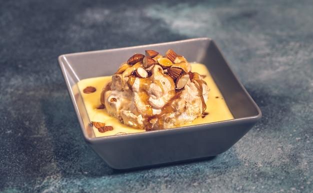 Sobremesa flutuante da ilha feita de merengue flutuando no creme de baunilha