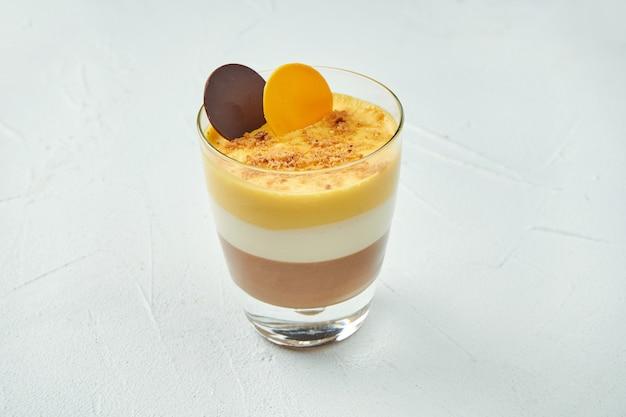 Sobremesa folhada em um copo com leite, chocolate e maracujá em uma superfície de textura branca