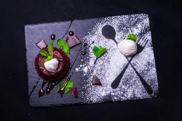 Sobremesa fondan de chocolate com menta e sorvete em um bacground de madeira. fondant de sobremesa de chocolate francês requintado. cupcakes com decorações para dia dos namorados