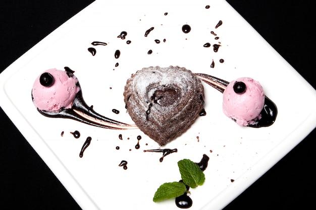 Sobremesa fondan de chocolate com sorvete em um prato branco sobre um fundo preto. fondan de sobremesa de chocolate francês requintado