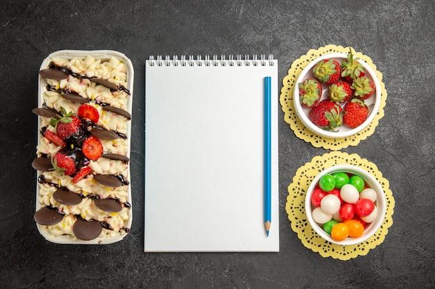 Sobremesa gostosa de vista de cima com biscoitos e morangos em fundo cinza escuro biscoito de nozes biscoito de frutas doces açúcar