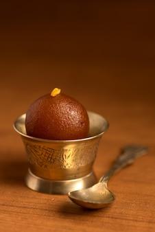 Sobremesa indiana ou prato doce: gulab jamun em tigela de cobre antigo com colher
