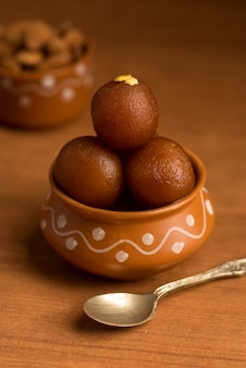 Sobremesa indiana ou prato doce gulab jamun em uma panela de barro com uma colher e frutas secas.