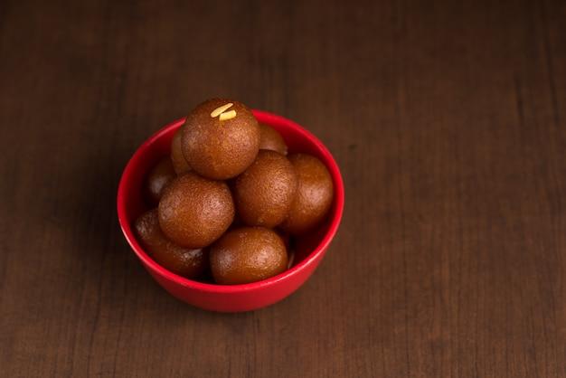 Sobremesa indiana ou prato doce gulab jamun em uma tigela de madeira.