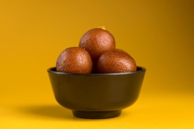 Sobremesa indiana ou prato doce: gulab jamun em uma tigela sobre fundo amarelo.