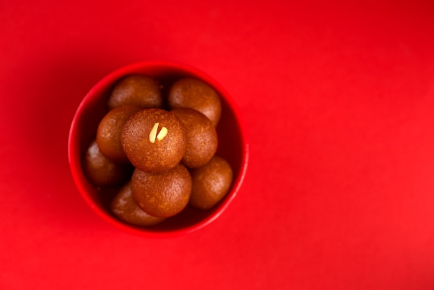Sobremesa indiana ou prato doce gulab jamun em uma tigela sobre um vermelho.