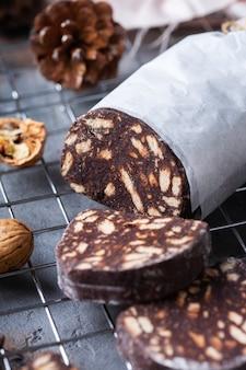 Sobremesa italiana tradicional - salame de chocolate de natal com biscoitos quebrados e nozes em uma mesa