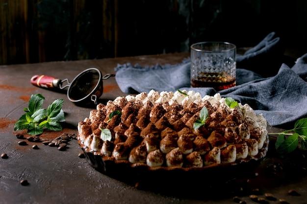 Sobremesa italiana tradicional tiramisu sem glúten caseiro polvilhada com cacau em pó decorado com folhas de hortelã, copo de uísque, guardanapo azul têxtil e grãos de café sobre fundo escuro de textura.