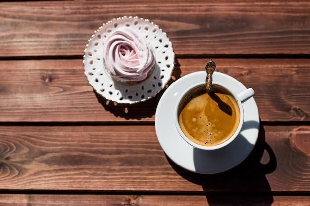 Sobremesa orgânica caseira, feita de purê de frutas e bagas, zéfiro ou marshmallow com copo de café isolado. conceito de bom dia romântico. copie o espaço