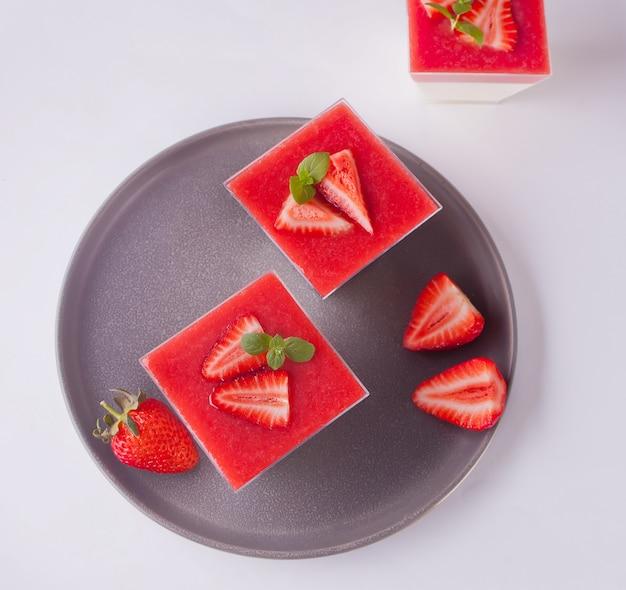 Sobremesa panna cotta com morangos frescos em branco