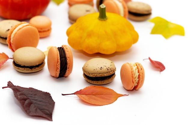 Sobremesa para o halloween. menu de ação de graças. macarons de pastelaria francesa. bolo de macarrão com chocolate e mascarpone em um fundo branco com abóboras e folhas de outono. foco seletivo suave. fechar-se