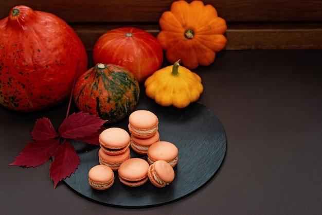 Sobremesa para o halloween. menu de ação de graças. macarons de pastelaria francesa. macaroons com chocolate e queijo mascarpone em um fundo preto com abóboras e folhas de outono. foco seletivo suave. copie o espaço