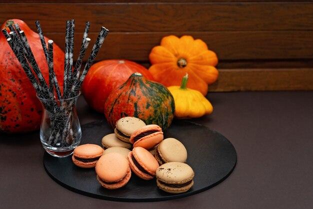 Sobremesa para o halloween. menu de ação de graças. macarons franceses. macaroons com chocolate contra um fundo preto com abóboras e palhas de coquetel eco. foco seletivo suave. copie o espaço