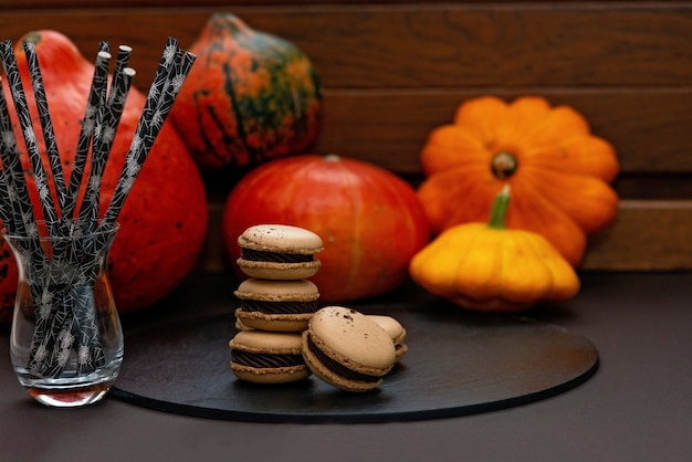 Sobremesa para o halloween. menu de ação de graças. macarons franceses. macaroons com chocolate em uma placa de massa de pedra contra um fundo preto com abóboras. foco seletivo suave.