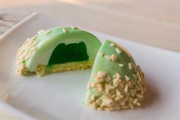 Sobremesa pequena com recheio. bolo glaceado de cor verde. bolo de musse com sabor a menta. gelatina e creme.