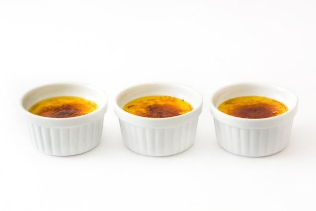 Sobremesa queimada francesa tradicional da nata com o açúcar caramelizado isolado no branco.