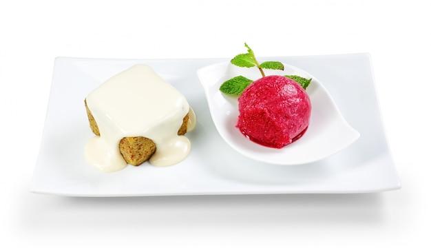 Sobremesa saborosa com sorvete em um prato em uma parede branca.