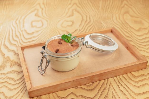 Sobremesa saborosa de tiramisu na bandeja de madeira fechar