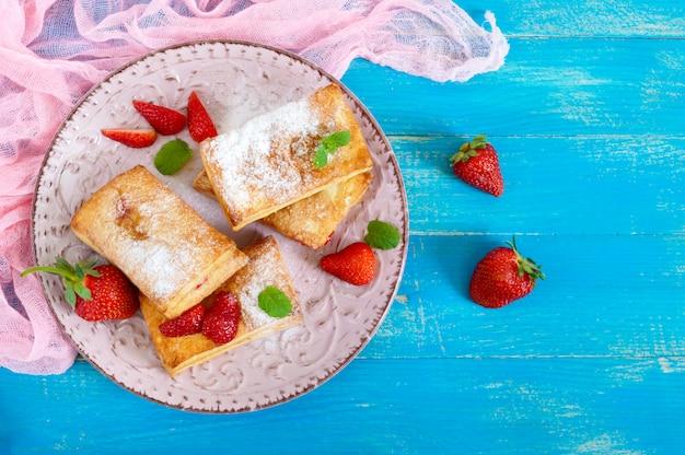 Sobremesa saborosa doce da massa folhada na placa no fundo de madeira. deliciosos biscoitos caseiros com geléia de morango, frutas e açúcar em pó. a vista de cima