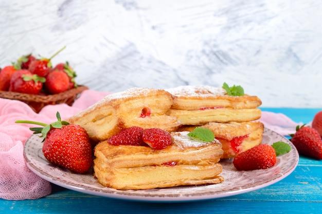 Sobremesa saborosa doce da massa folhada na placa no fundo de madeira. deliciosos biscoitos caseiros com geléia de morango, frutas e açúcar em pó.