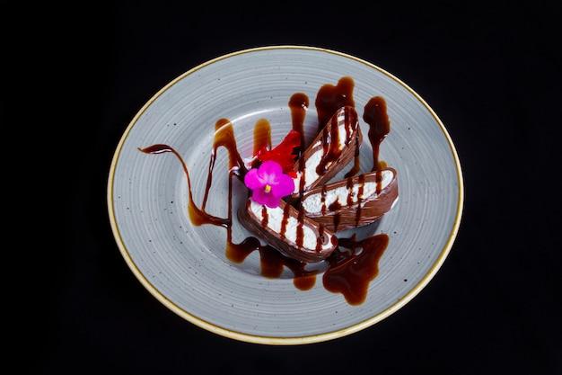 Sobremesa saborosa. sorvete de baunilha branco-creme de chocolate, decorado com uma flor decorativa, sobre um fundo preto