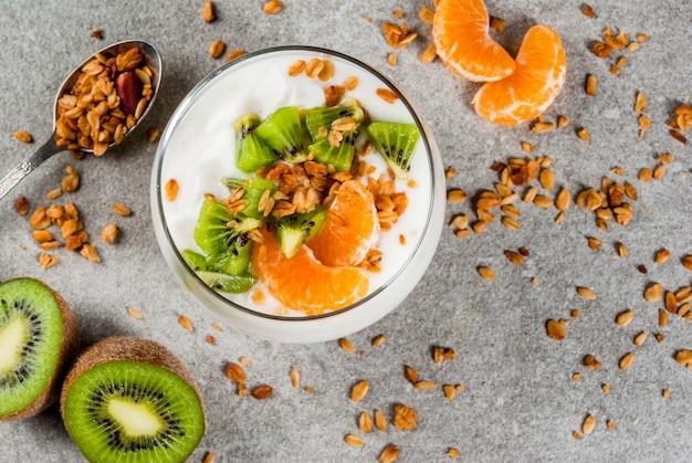 Sobremesa saudável de granola de iogurte de tangerina e kiwi no café da manhã, com ingredientes, mesa de pedra cinza, cópia espaço vista superior