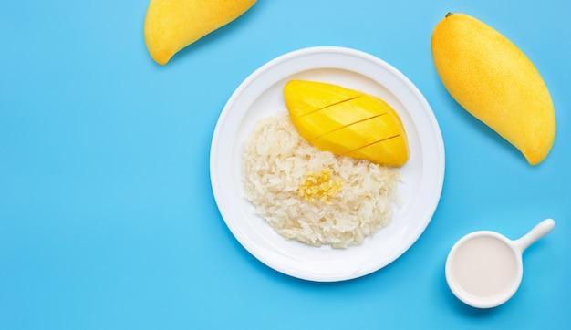 Sobremesa tailandesa, arroz doce com manga e leite de coco sobre fundo azul.