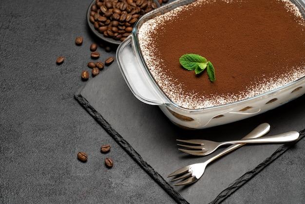 Sobremesa tiramisu italiana tradicional em assadeira de vidro em uma tábua de servir de pedra sobre um fundo de concreto ou mesa