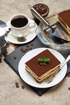 Sobremesa tiramisu tradicional italiana em assadeira de vidro e porção em mesa de concreto cinza