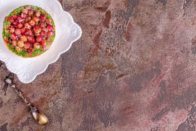 Sobremesa torta de morango selvagem no prato branco com colher vintage em fundo de mármore marrom