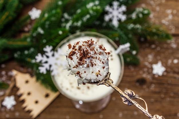 Sobremesa tradicional de ameixa com nozes e chantilly com açúcar. conceito de doce presente de ano novo. superfície de tábuas de madeira, foco seletivo