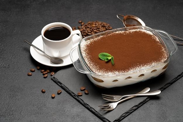 Sobremesa tradicional italiana tiramisu em assadeira de vidro e xícara de café expresso quente fresco em um fundo de concreto ou mesa