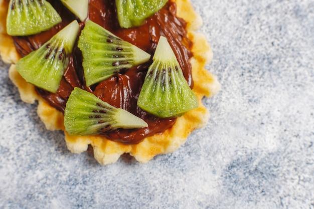 Sobremesas caseiras com mirtilos, fatias de kiwi e sementes de romã.