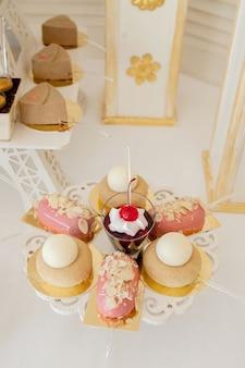Sobremesas com frutas, mousse, biscoitos. diferentes tipos de doces, pequenos bolos coloridos, macaron e outras sobremesas no buffet. barra de chocolate para o aniversário.