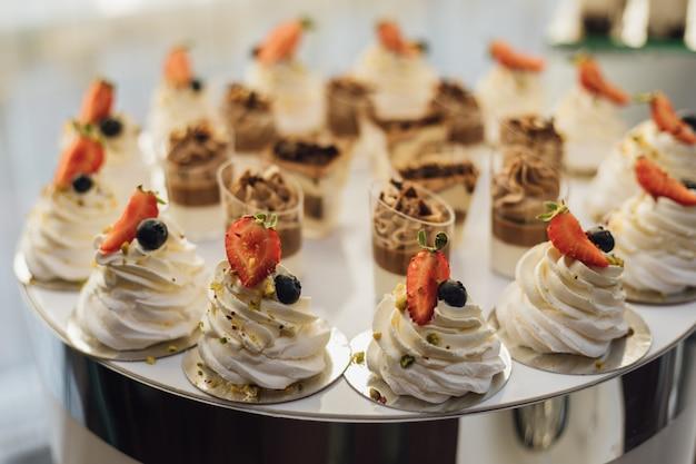 Sobremesas cremosas saborosas, decoradas com fatias de morango e tiramisu