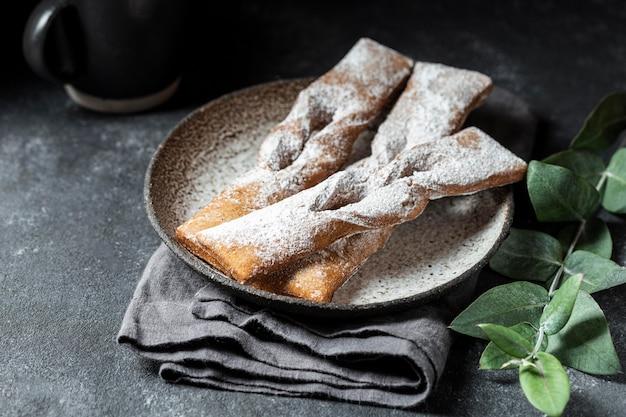 Sobremesas de alto ângulo cobertas de açúcar de confeiteiro com planta