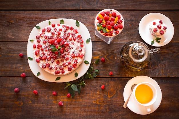 Sobremesas de framboesa com chá de ervas na mesa de madeira