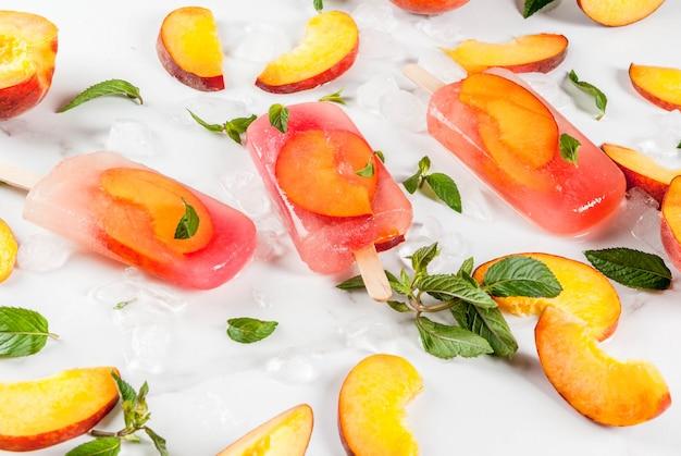 Sobremesas de verão. bebidas congeladas. picolés de frutas doces de chá de pêssego congelado com hortelã. em uma mesa de mármore branco, com ingredientes pêssegos, hortelã, gelo.