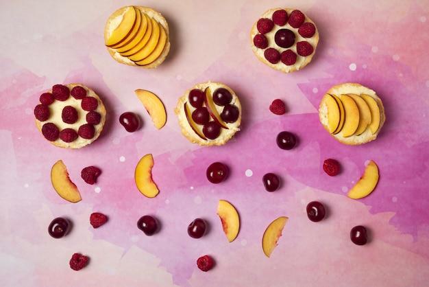 Sobremesas de verão com frutas fatiadas e bagas em fundo rosa