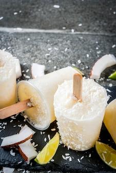 Sobremesas de verão. comida de dieta vegana. picolés de sorvete de frutas caseiras de coco e limão no palito. na mesa de pedra preta, copyspace