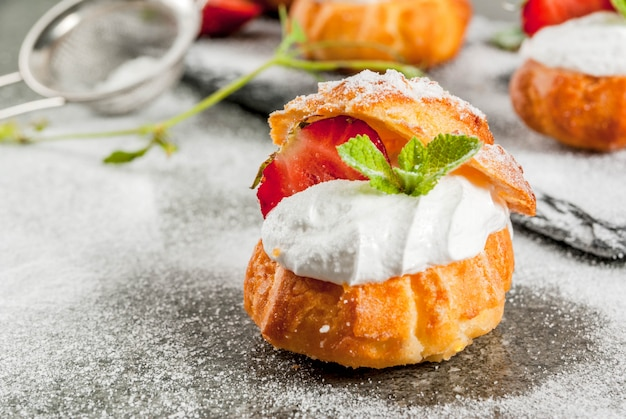 Sobremesas de verão. cozimento caseiro. profiteroles de bolo com chantilly, morangos frescos, menta e polvilhar de açúcar em pó. em uma mesa de pedra preta. copyspace