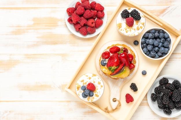 Sobremesas doces com frutas frescas em fundo de madeira.
