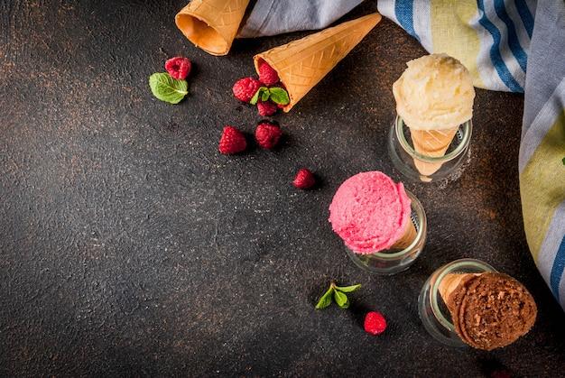 Sobremesas doces de verão e sobremesas, vários tipos de sorvete em cones rosa (framboesa), baunilha e chocolate com menta no escuro