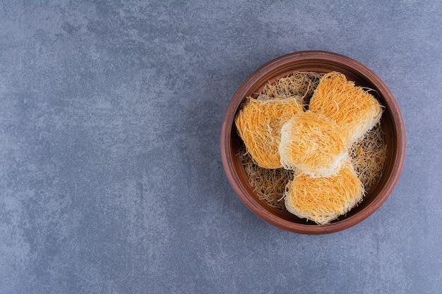 Sobremesas doces turcas em um prato de barro sobre uma pedra.