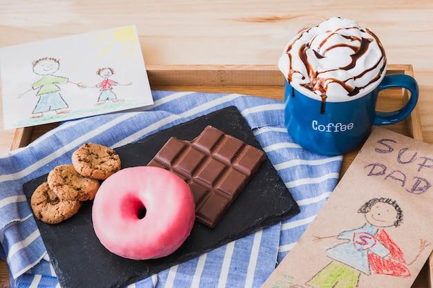 Sobremesas e chocolate quente perto de fotos na bandeja