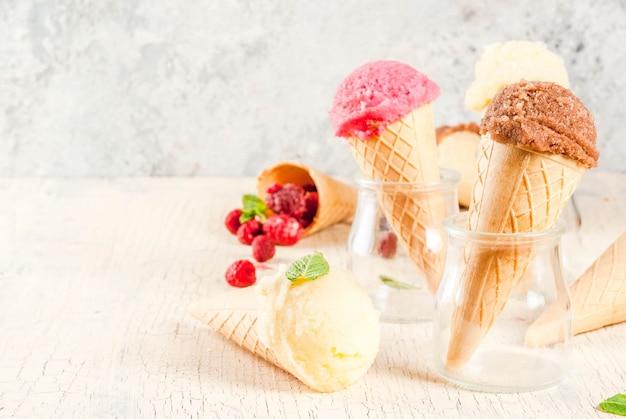 Sobremesas e frutos doces de verão vários tipos de sabor de sorvete em baunilha de cones rosa (framboesa) e chocolate com hortelã na luz de fundo de concreto
