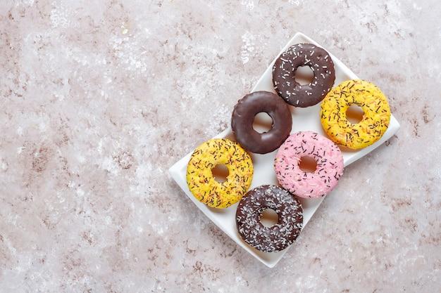 Sobremesas variadas com cobertura de chocolate, glacê rosa e granulado.